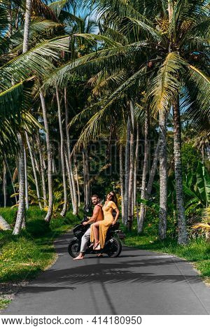 A Couple In Love On A Scooter Among The Palm Trees. Happy Couple On Vacation In Bali. The Couple Tra