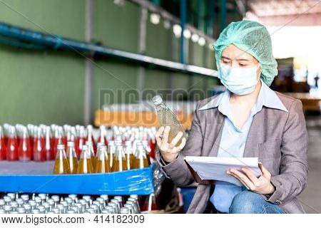 An Asian Attractive Woman Factory Manager Wearing A Masks, Is Counting Stock And Check Product Quali