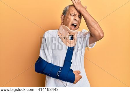 Handsome mature senior man wearing cervical collar and arm on sling surprised with hand on head for mistake, remember error. forgot, bad memory concept.