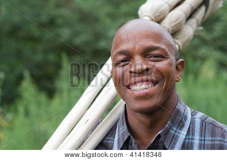 Fotografía de stock de un vendedor de escoba de pequeña empresa empresario sudafricano negro sonriente