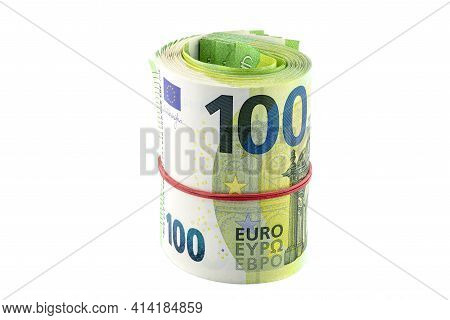 Macro Shot Of The European Union 100 Euro Banknote, Rolled Up Into A Rubber Band, Isolated On A Whit