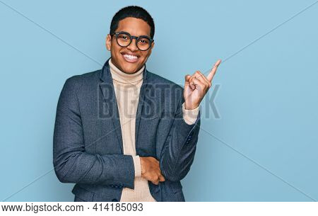 Young handsome hispanic man wearing business jacket and glasses smiling happy pointing with hand and finger to the side