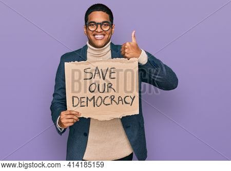 Young handsome hispanic man holding save our democracy protest banner smiling happy and positive, thumb up doing excellent and approval sign