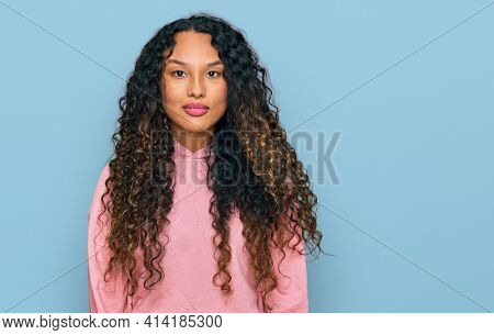 Young hispanic woman with curly hair wearing casual sweatshirt with serious expression on face. simple and natural looking at the camera.