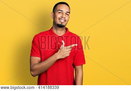 Young african american man wearing casual polo smiling cheerful pointing with hand and finger up to the side