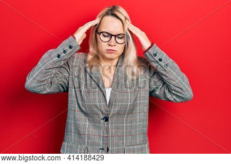 Beautiful caucasian blonde woman wearing business jacket and glasses with hand on head, headache because stress. suffering migraine.