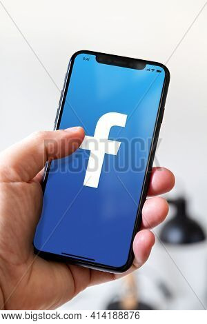 Paris - France - March 23, 2021 : Hand Holding Iphone Smartphone With Facebook Logo