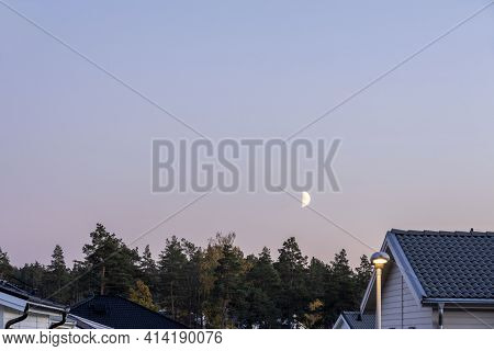 Beautiful View Of The Natural Landscape On A Summer Night. Roofs Of Villas, Forest, Moon, Blue Sky A