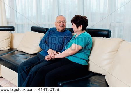 60s Spouses Photo Shooting Indoors. Overjoyed Mature Husband And Wife Relax On Couch Have Fun Laughi