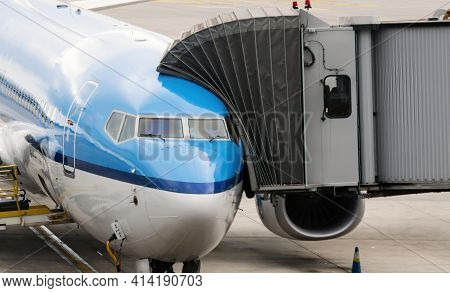 Jet Bridge Attached To The Fuselage Of A Commercial Aircraft To Allow Travelers To Board. Passenger