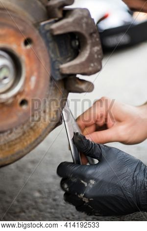 Mechanic Working At A Car Worn And Rusty Brake Disk And Caliper