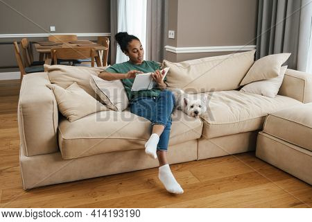 Smiling black woman reading book while sitting with her dog on sofa at home