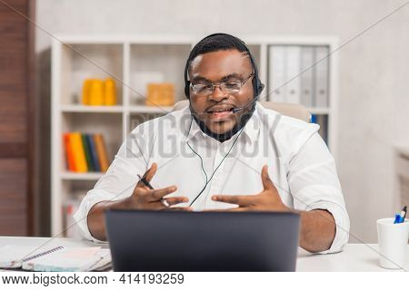 Workplace of freelancer. African-American man works at home office using computer, headset and other devices. Employee is having a conference call. Remote job.