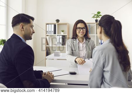 Friendly Bank Worker Giving Pen To Sign Contract Promising Good Deal To Client