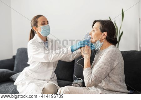 Female Doctor Wearing A White Gown And A Face Mask, Putting Oxygen Mask On The Face Of A Senior Woma