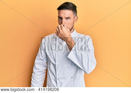 Handsome man with beard wearing professional cook uniform smelling something stinky and disgusting, intolerable smell, holding breath with fingers on nose. bad smell