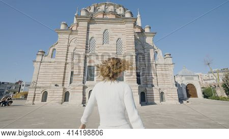 Beautiful Woman Goes To Mosque. Action. Rear View Of Beautiful Woman Walking In Front Of Mosque. Att