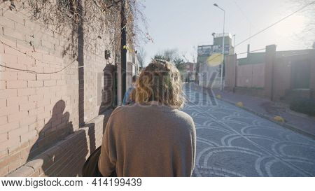 Woman Walking Through Residential Area. Action. Rear View Of Woman Walking By Stone Fences In Reside