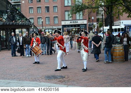 BOSTON, MASSACHUSETTS - 16 OCT 2011: Tourists watch Revolutionary War Soldiers re-enactment in Quincy Market.