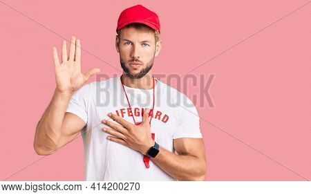 Young caucasian man wearing lifeguard t shirt holding whistle swearing with hand on chest and open palm, making a loyalty promise oath