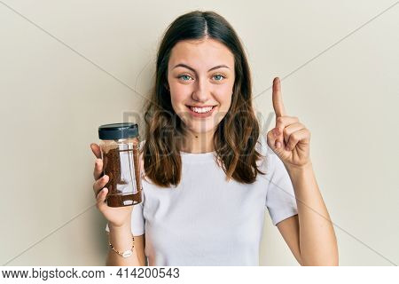 Young brunette woman holding soluble coffee smiling with an idea or question pointing finger with happy face, number one