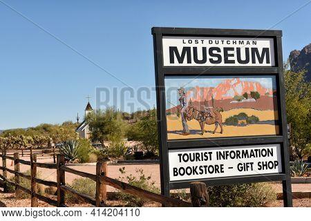 APACHE JUNCTION, ARIZONA - 8 DEC 2016: Lost Dutchman Museum sign with the Elvis Memorial Chapel in the background, in Apache Junction, Arizona.