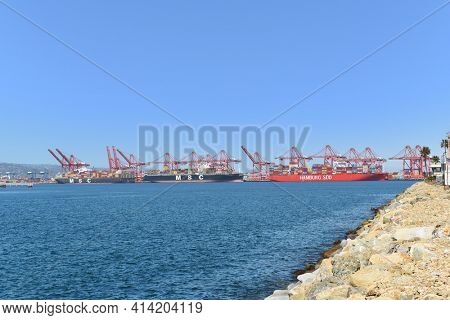 LONG BEACH, CALIFORNIA - 20 MAR 2021: Container ships being unloaded at the Port of Long Beach.