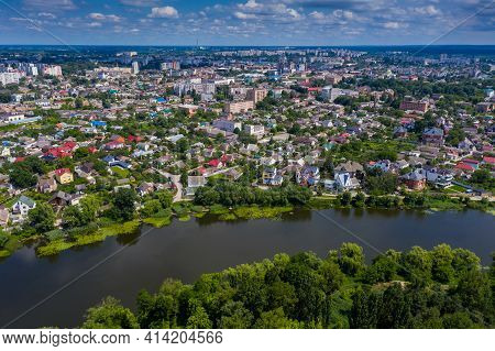 Beautiful Summer Top View Of The City. Roofs Of Houses, River, Trees With Green Leaves.
