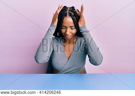 Beautiful hispanic woman wearing casual clothes sitting on the table suffering from headache desperate and stressed because pain and migraine. hands on head.