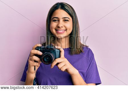 Young latin woman using reflex camera smiling with a happy and cool smile on face. showing teeth.