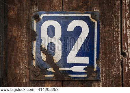Weathered Grunge Square Metal Enamelled Plate Of Number Of Street Address With Number 82