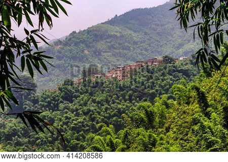 Rural Village Atop A Hill In The Midst Of Lush Tropical Forest In Yunnan, China