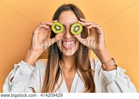 Young beautiful woman holding slice of kiwi over eyes sticking tongue out happy with funny expression.