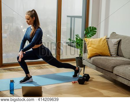 Brunette in turquoise jumpsuit does exercise standing in yoga warrior pose on mat by panoramic windows with view on city in room