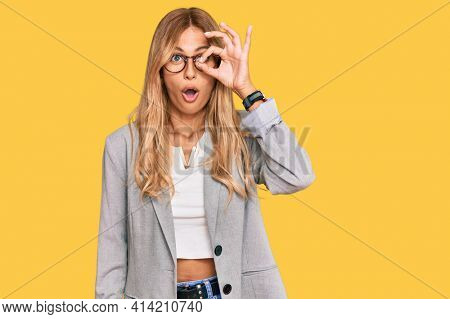 Beautiful blonde young woman wearing business clothes doing ok gesture shocked with surprised face, eye looking through fingers. unbelieving expression.