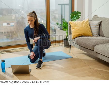 Sportive brunette with ponytail standing on right knee watches video lesson on laptop near panoramic window and green pot plant