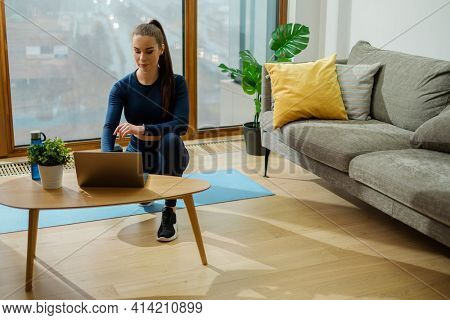 Young sportive woman with brown ponytail in turquoise jumpsuit browses internet on laptop standing on wooden coffee table in lodge
