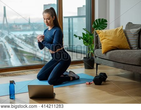 Sportive brunette practices exercise with workout video on laptop near panoramic window with city road view in spring in room