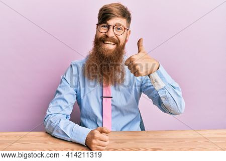 Young irish redhead man wearing business shirt and tie sitting on the table doing happy thumbs up gesture with hand. approving expression looking at the camera showing success.
