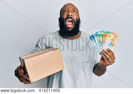 Young african american man holding delivery box and swiss franc banknotes angry and mad screaming frustrated and furious, shouting with anger looking up.