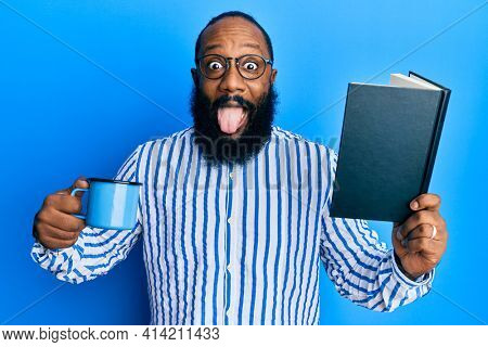 Young african american man reading book and drinking a cup of coffee sticking tongue out happy with funny expression.