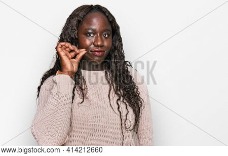 Young african woman wearing wool winter sweater mouth and lips shut as zip with fingers. secret and silent, taboo talking