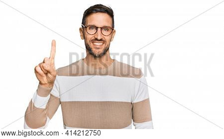 Handsome man with beard wearing casual clothes and glasses showing and pointing up with finger number one while smiling confident and happy.