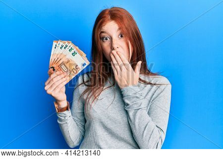 Young red head girl holding bunch of 50 euro banknotes covering mouth with hand, shocked and afraid for mistake. surprised expression
