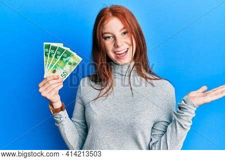 Young red head girl holding 50 israel shekels banknotes celebrating achievement with happy smile and winner expression with raised hand