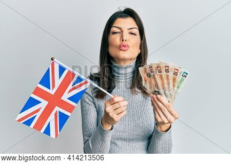 Young hispanic woman holding united kingdom flag and pounds banknotes looking at the camera blowing a kiss being lovely and sexy. love expression.
