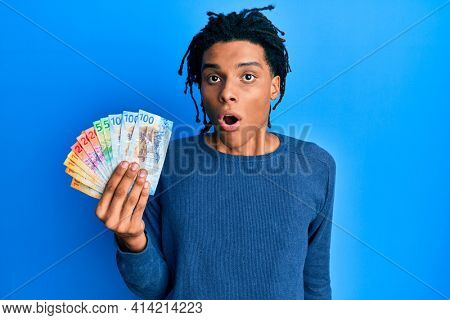 Young african american man holding swiss franc banknotes scared and amazed with open mouth for surprise, disbelief face
