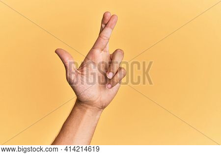 Arm and hand of caucasian man over yellow isolated background gesturing fingers crossed, superstition and lucky gesture, lucky and hope expression
