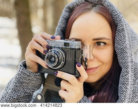 Young Woman In Gray Coat Photographing On Old Photo Camera In Forest. Pretty Female Taking Photos Wi