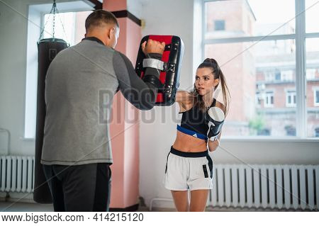 Beautiful Woman Boxing Combat Bag With Sport Trainer Together. Girl Boxer Exercising Box Punch With